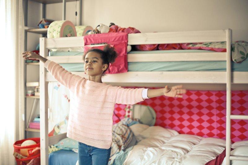 Ein Mädchen steht vor einem Hochbett