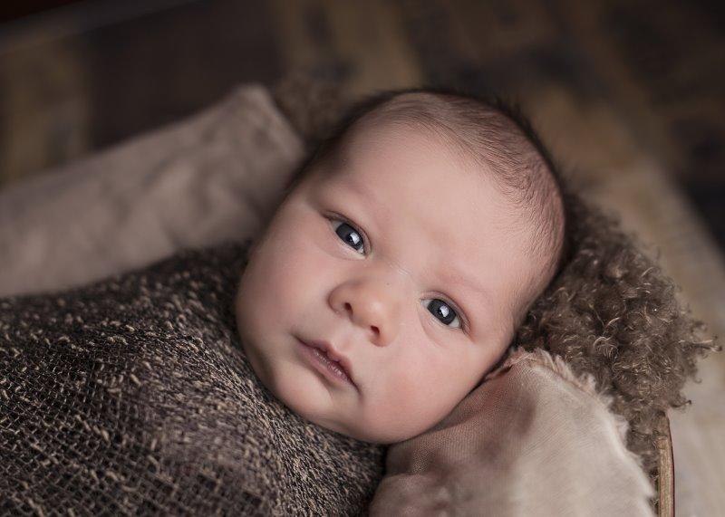 Ein Neugeborenes in einem Pucksack aus Wolle