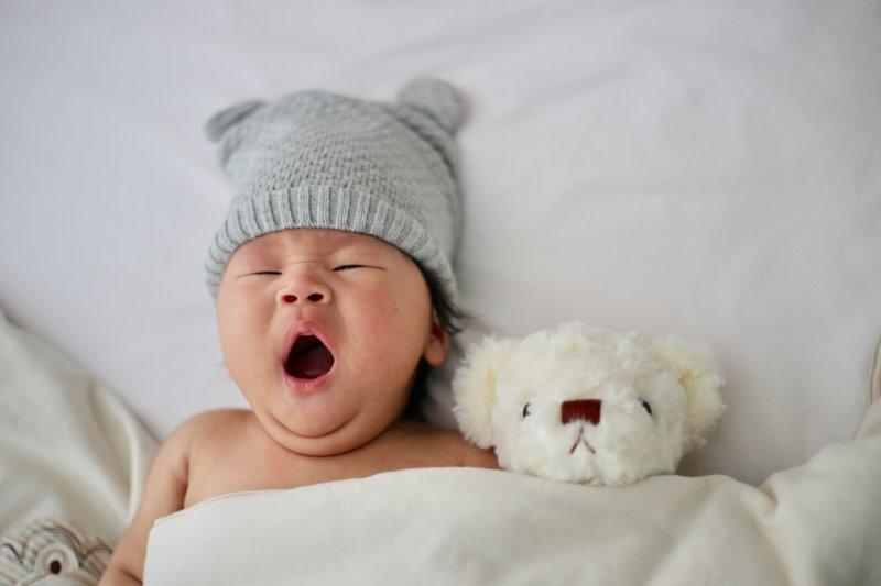 Ein gähnendes Baby mit einer grauen Strickmütze und einem weißen Teddybär