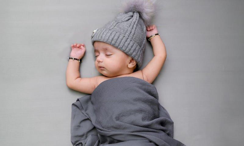 Ein schlafendes Baby mit Wollmütze und grauer dünner Decke