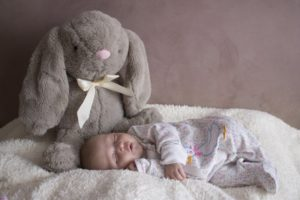 Ein schlafendes Baby in seinem Strampelanzug mit einem grauen großen Stoffhasen