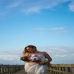 Frau stillt Baby auf einer Brücke