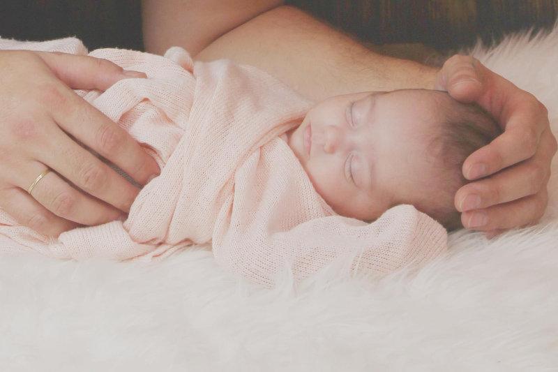 Schlafendes Baby im Wickeltuch eingepuckt.